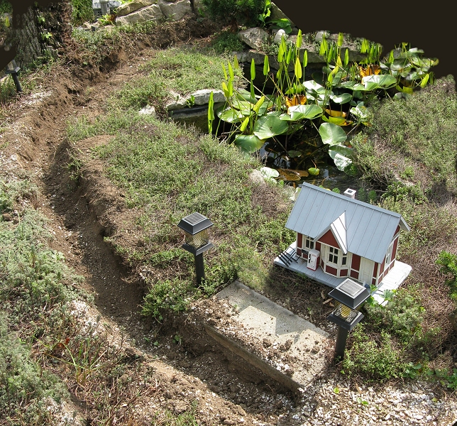 My garden railroad, with the original gravel trench scooped out to be replaced with concrete.  Click for bigger photo.